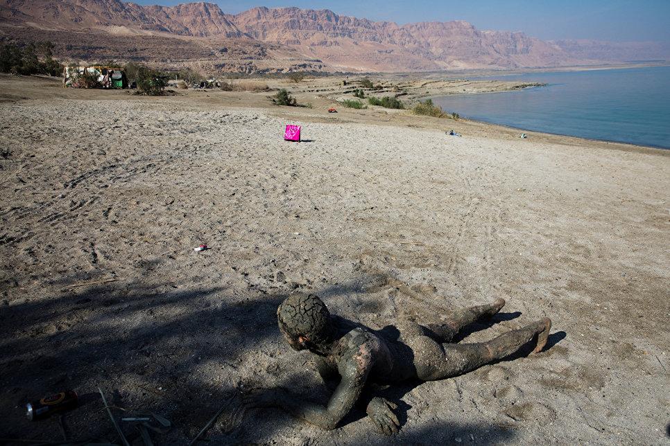Человек, покрытый грязью из Мертвого моря, отдыхает на берегу