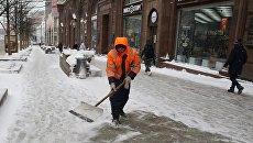 Сотрудник коммунальных служб убирают последствия снегопада на Тверской улице в Москве. Архивное фото