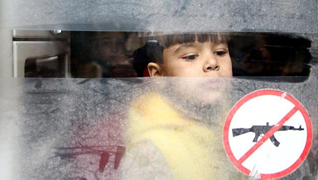 Ребенок смотрит в окно автобуса во время эвакуации из осажденного города в Восточной Гуте, Сирия. 13 марта 2018