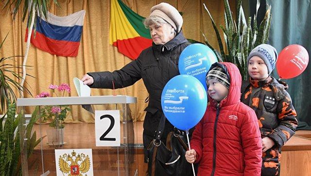 Женщина опускает бюллетень в урну на выборах президента Российской Федерации на избирательном участке в Чите. 18 марта 2018