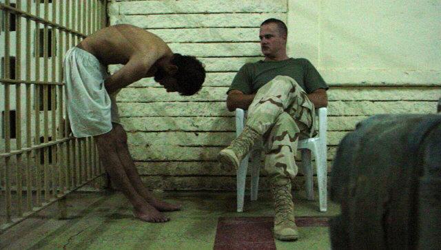Американский военный и заключенный тюрьмы Абу-Грейб в Багдаде, Ирак. 2003