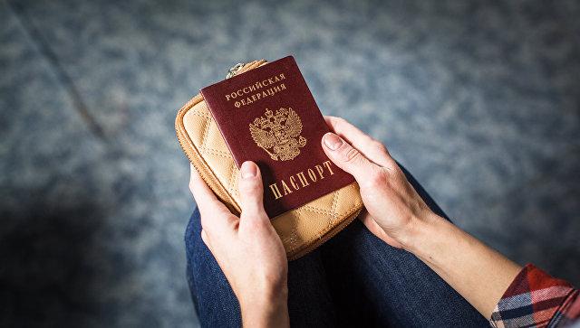 Девушка держит российский паспорт. архивное фото