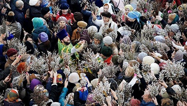Священнослужитель и верующие в праздник Входа Господня в Иерусалим в Спасо-Преображенском кафедральном соборе Хабаровска