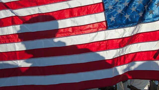 Военный на фоне флага США . Архивное фото