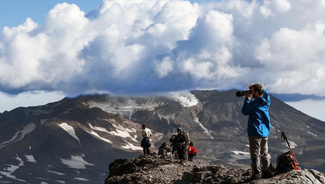 Туристы смотрят на вулкан Мутновский с вершины вулкана Горелого
