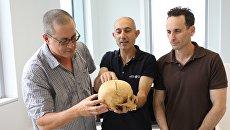 Профессор Боаз Зиссу, доктор Йосси Нагар и доктор Хаим Коэн с найденным в пещере черепом