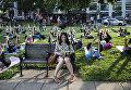 Женщина читает книгу на фоне группы, практикующей йогу в парке. Вашингтон, США