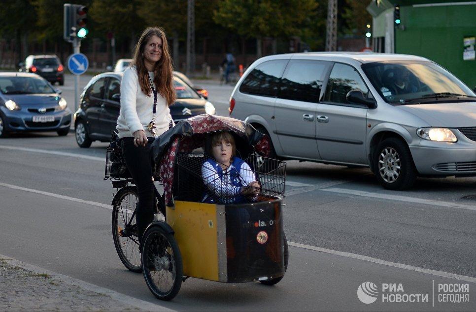 Девушка на велосипеде с ребенком на одной из улиц Копенгагена.