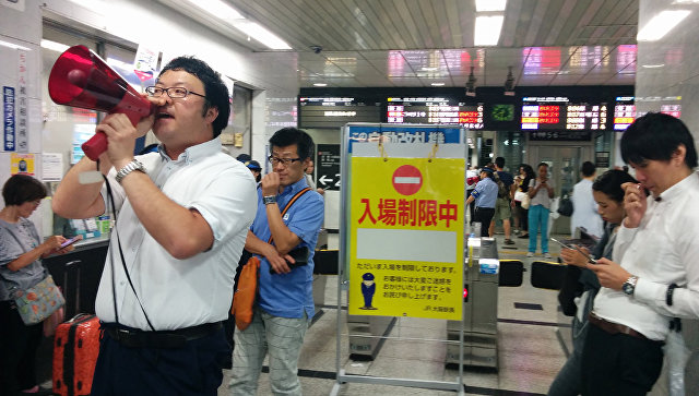 Сотрудник станции делает объявление пассажирам после землетрясения в Японии. 18 июня 2018