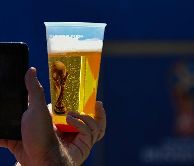 Болельщик фотографирует стакан пива с символикой чемпионата мира по футболу