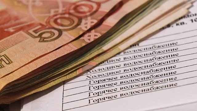Денежные купюры и квитанция за оплату коммунальных услуг. Архивное фото