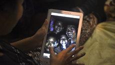 Члены семьи смотрят на фотографии пропавших мальчиков, которые сделали спасатели-дайверы в пещере, когда все члены детской футбольной команды и их тренер были найдены живыми. Архивное фото