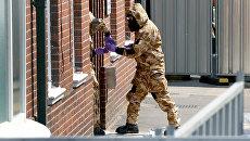 Сотрудники британских спецслужб в защитных костюмах у жилого дома в Солсбери. Архивное фото