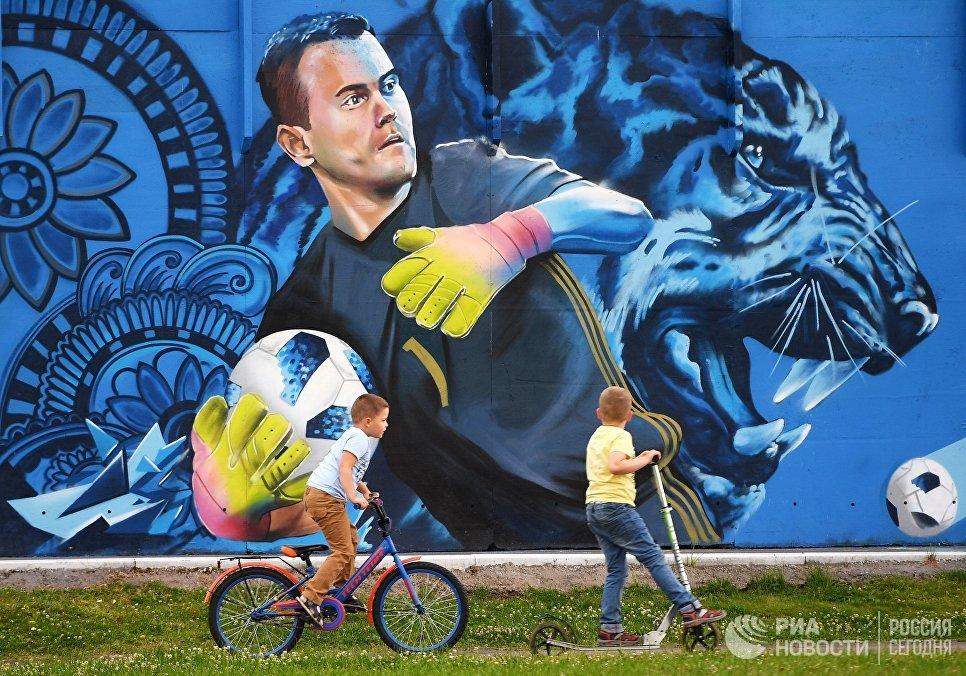 Дети рассматривают граффити с изображением вратаря сборной России по футболу Игоря Акинфеева в Щелково