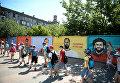 Дети на фоне граффити-портретов футболистов восьми сборных на бетонном заборе на пересечении улиц Советской и Комсомольской в Волгограде в рамках проведения чемпионата мира по футболу 2018