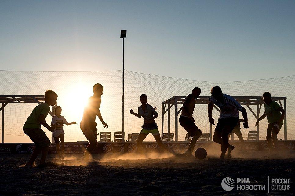 Отдыхающие на пляже играют в футбол в поселке Оленевка