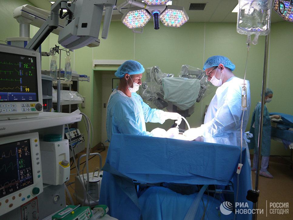 Хирургическая бригада делает надрезы на животе пациента, через которые в его брюшную полость вводятся две камеры
