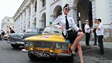 Девушка в форме сотрудницы Госавтоинспекции у автомобиля «Жигули» ВАЗ-2103 ГАИ перед началом гонки ГУМ-авторалли Gorkyclassic - 2018 в Москве