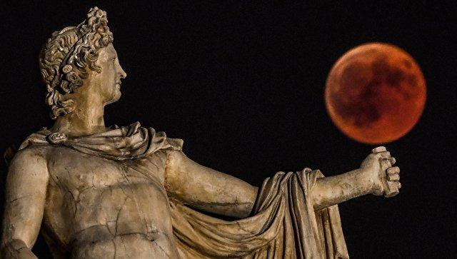 Луна во время затмения рядом со статуей древнегреческого Бога Аполлона в центре Афин, Греция. 27 июля 2018