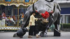 Девушка проходит мимо статуи быка в Пекине