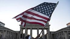 Флаг США во время акции протеста у Бранденбургских ворот в Берлине. Архивное фото