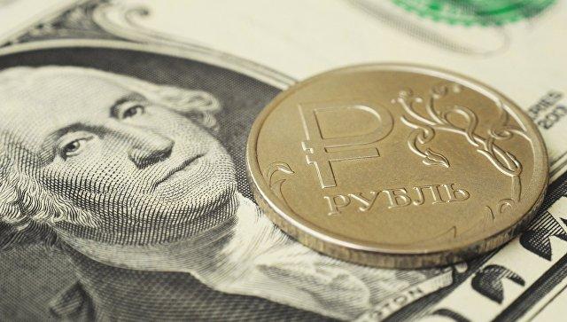 Монета номиналом один рубль на банкноте один доллар США. Архивное фото
