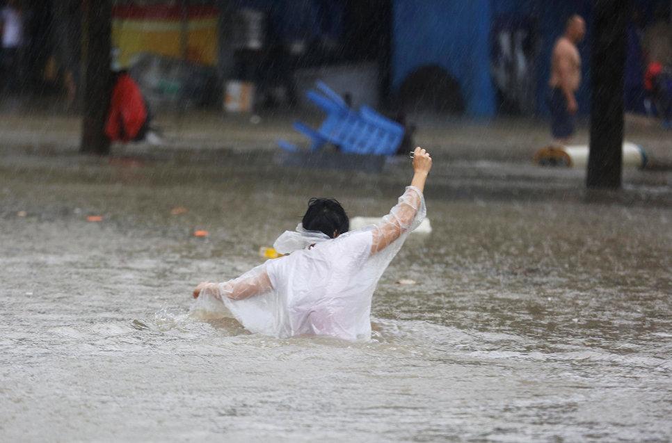 Женщина на улице города Чжуншань, провинции Гуандун во время тайфун Мангхут. 16 сентября 2018 года