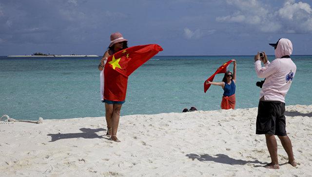 Туристы на пляже в провинции Хайнань в Китае