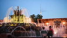 Девушки отдыхают у фонтана Каменный цветок на ВДНХ в Москве