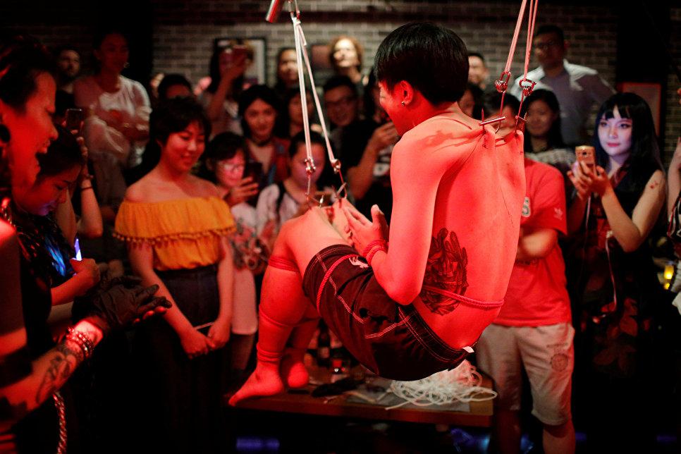 Зрители наблюдают за человеком, подвешенным за кожу художником в технике боди-арт Вэй Йилаиен в одном из баров Шанхая