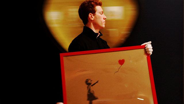 Сотрудник с работой художника Бэнкси Девочка и воздушный шар в аукционном доме Bonhams в Лондоне