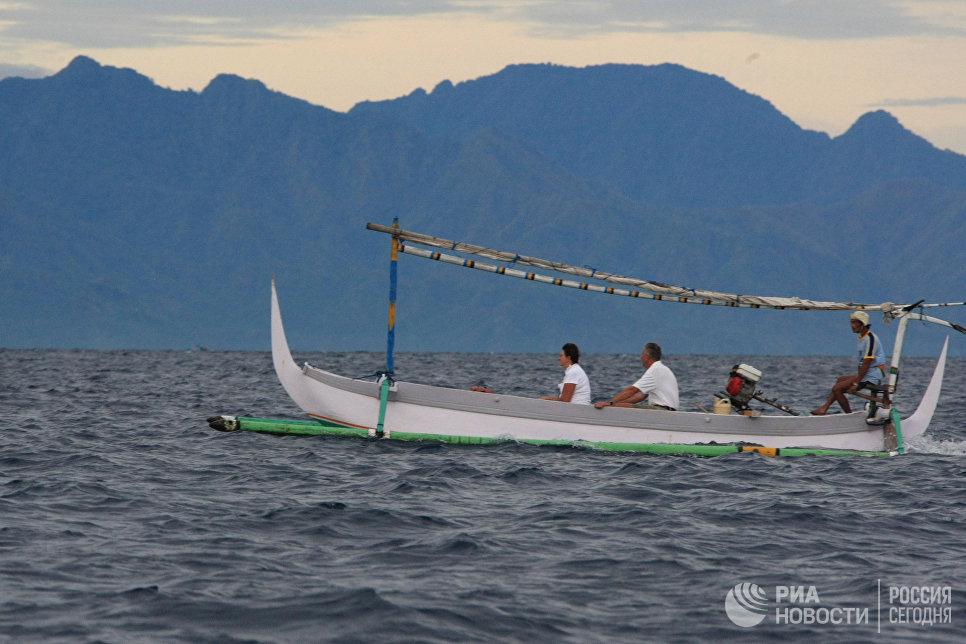 Туристы катаются на лодке у побережья острова Бали.