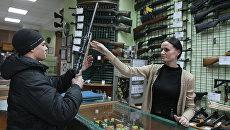 Продавец консультирует покупателя в оружейном магазине. Архивное фото