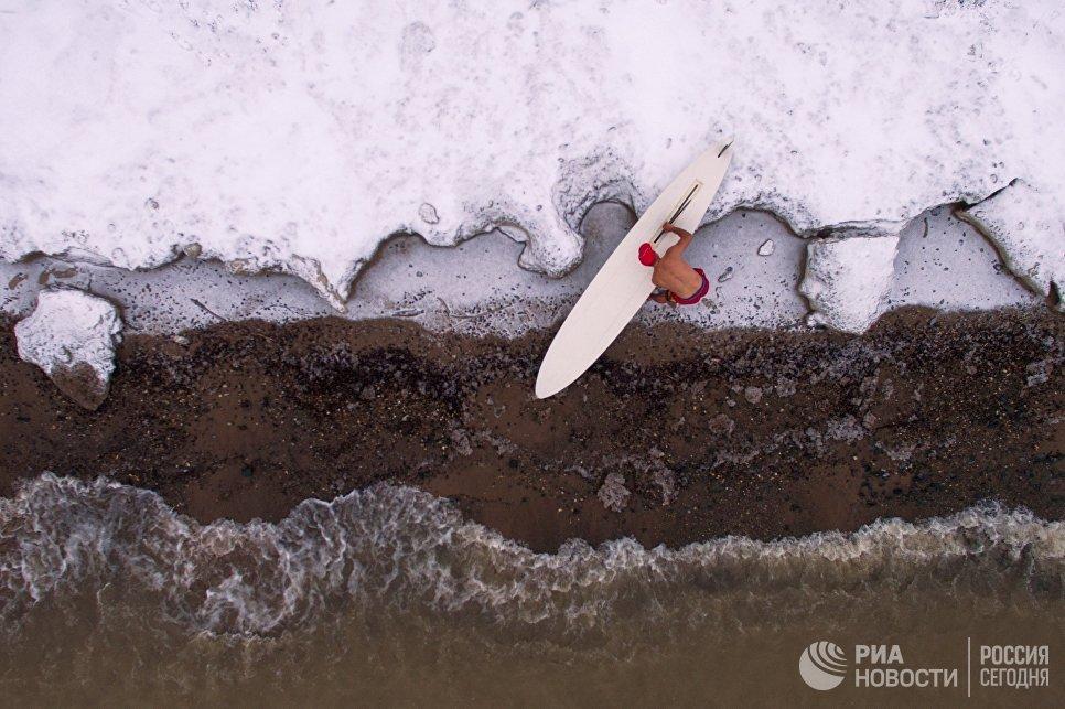 Спортсмен Александр Орлов закрывает сезон виндсерфинга на серф-станции Бумеранг на берегу водохранилища Новосибирской ГЭС при температуре около -5С