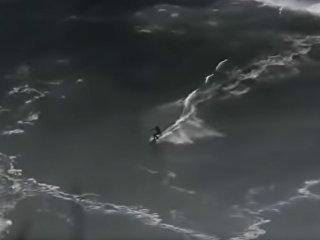 Кадр из видео, на котором серфер бопадает под огромную волну в Португалии