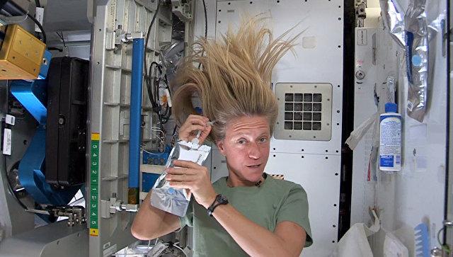 Астронавт Карен Найберг моет голову на борту МКС