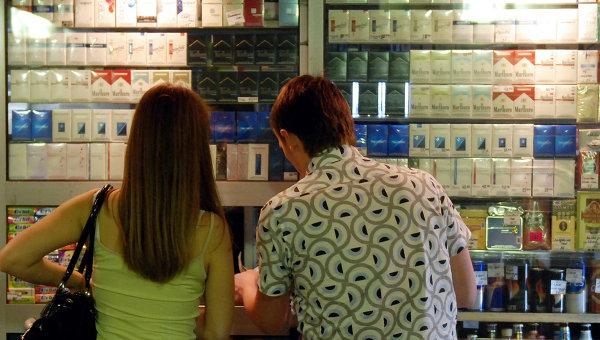 Молодые люди выбирают сигареты в табачном ларьке