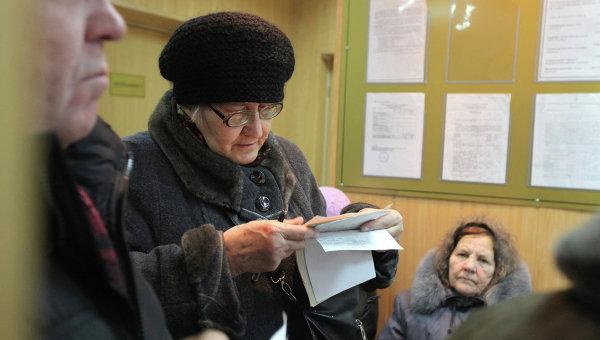Женщина проверяет правильность квитанции за услуги ЖКХ. Архив