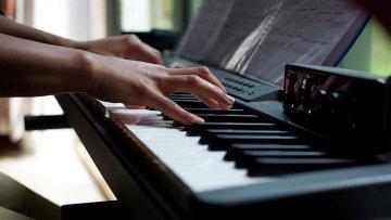 Девушка играет на фортепьяно, архивное фото