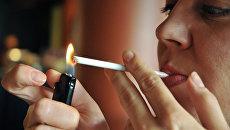 Девушка прикуривает сигарету