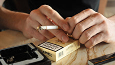 Мужчина держит в руках сигарету