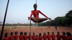 Девушка демонстрирует индийскую гимнастику Mallakhamb