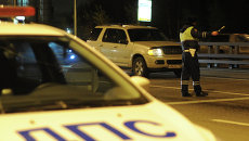 Сотрудник дорожно-патрульной службы ГИБДД останавливает автомобиль