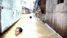 Люди по шею в воде передвигались по улицам Джакарты из-за наводнения