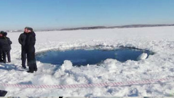 Сотрудники правоохранительных органов, экологи и специалисты МЧС на месте падения осколка метеорита в Челябинской области