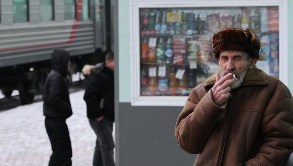 Мужчина курит на платформе. Архивное фото