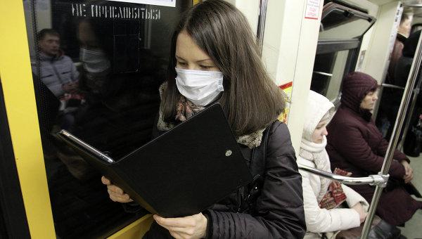 Девушка в защитной маске читает электронную книгу в московском метро