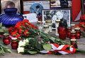 Поминальные свечи, цветы и фотографии жертв у памятного камня, установленного на месте крушения польского самолета Ту-154