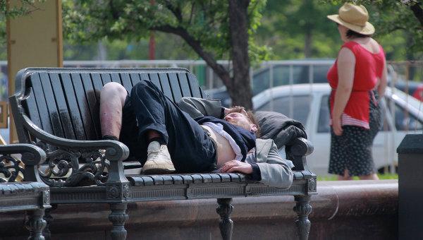 Бездомный спит на скамейке