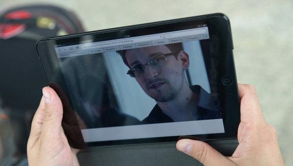 Журналист изучает фото бывшего сотрудника ЦРУ Эдварда Сноудена, архивное фото
